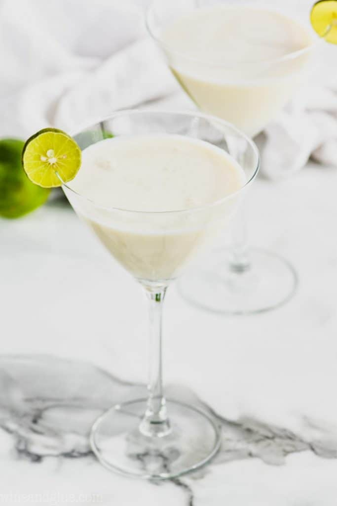 angled overhead view of a martini glass filled with white key lime pie martini recipe with another glass and some limes in the background