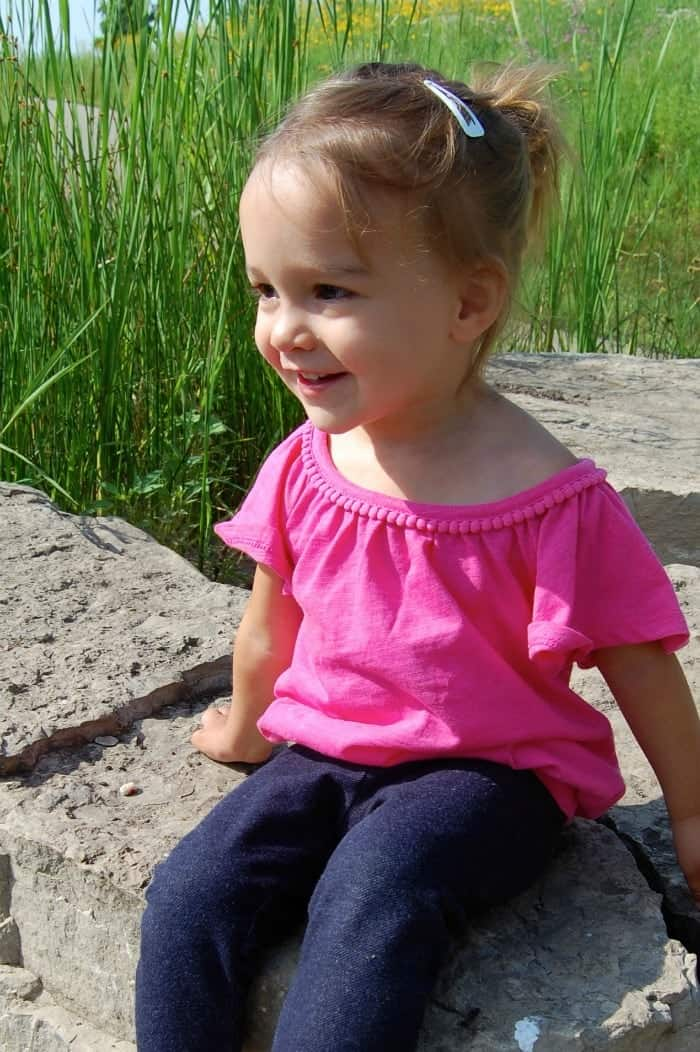 Picture of toddler girl in a pink top and blue pants.