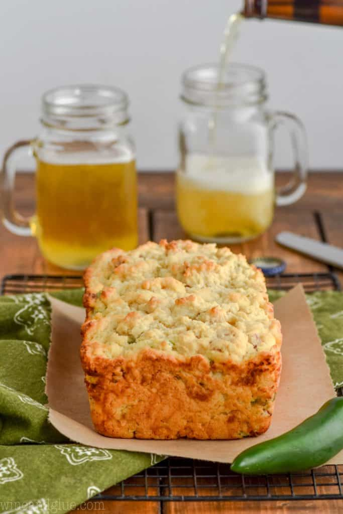 front on view of a loaf of jalapeno popper beer bread with beer mugs in the background