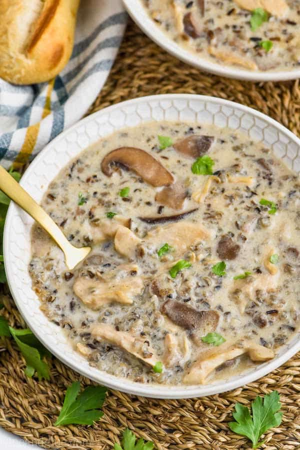 overhead view of creamy chicken and wild rice soup recipe in a bowl, garnished with parsley