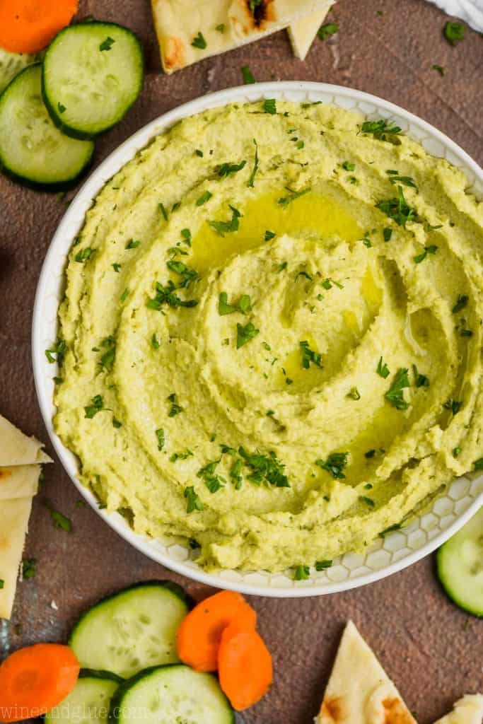 overhead view of a white bowl on a brown surface filled with edamame hummus recipe, garnished with parsley and oil and surrounded by cut vegetables and triangles of naan bread
