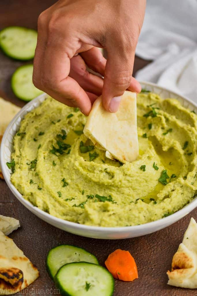 woman dipping a wedge of naan bread into a edamame hummus bowl