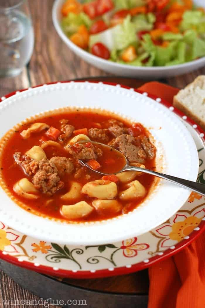 A bowl of the Spicy Sausage and Tortellini Soup with a side of a salad and a bread slice