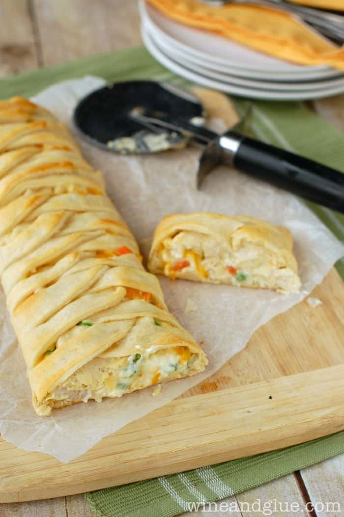 pulled back look of a chicken pot pie crescent braid on a cutting board with the front cut off