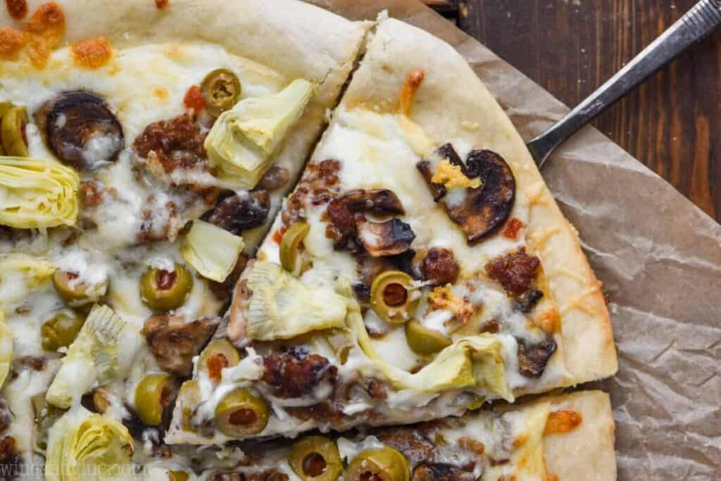 landscape photo of a white pizza topped with olives, artichokes, sausage, and mushrooms, one piece coming out