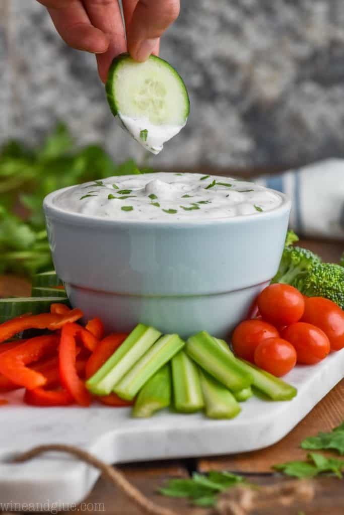 cucumber being dipped into healthy vegetable dip with vegetables around it