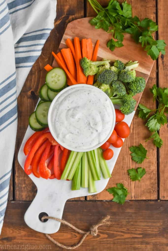 overhead view of vegetarian vegetable dip on a board with cut up vegetables