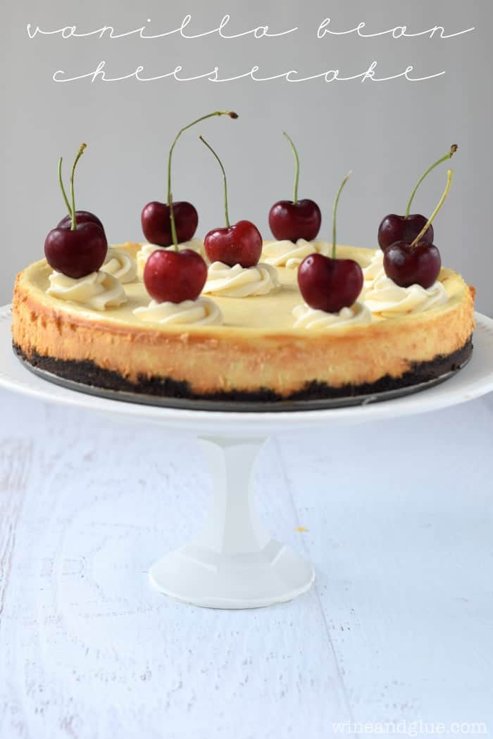 Vanilla Bean Cheesecake served on a platter with cherries on top.