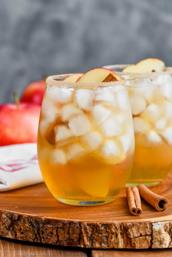 two glasses of the best apple margarita recipe on a wood tray with apples and cinnamon sticks