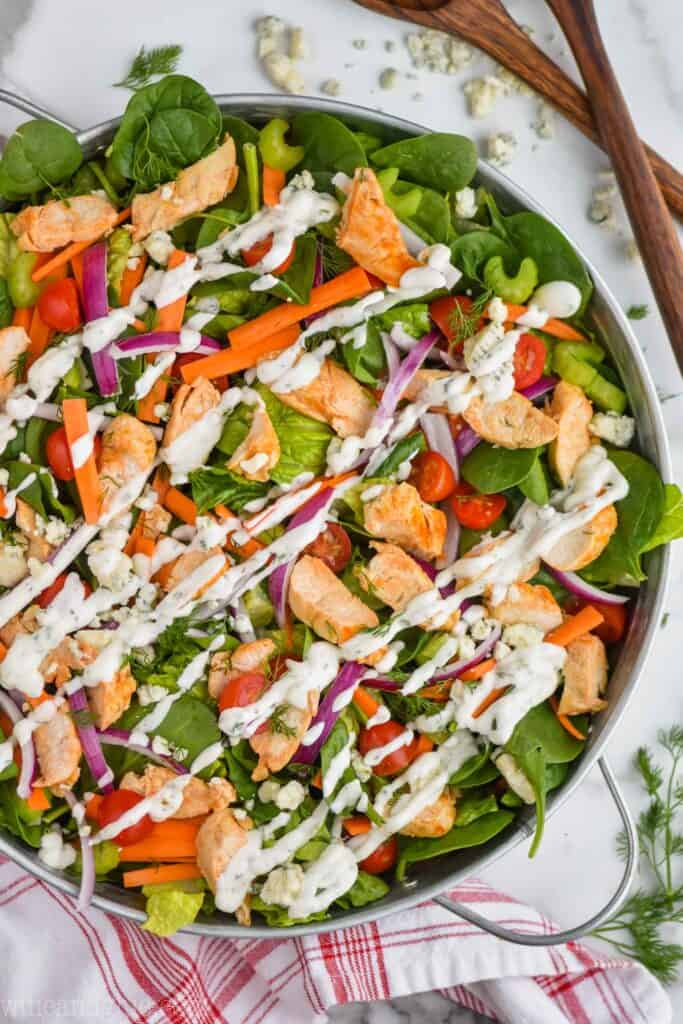 overhead view of a buffalo chicken salad dressed with ranch dressing in a large metal tray with blue cheese, wooden serving utensils, fresh dill, and a red and white napkin around it