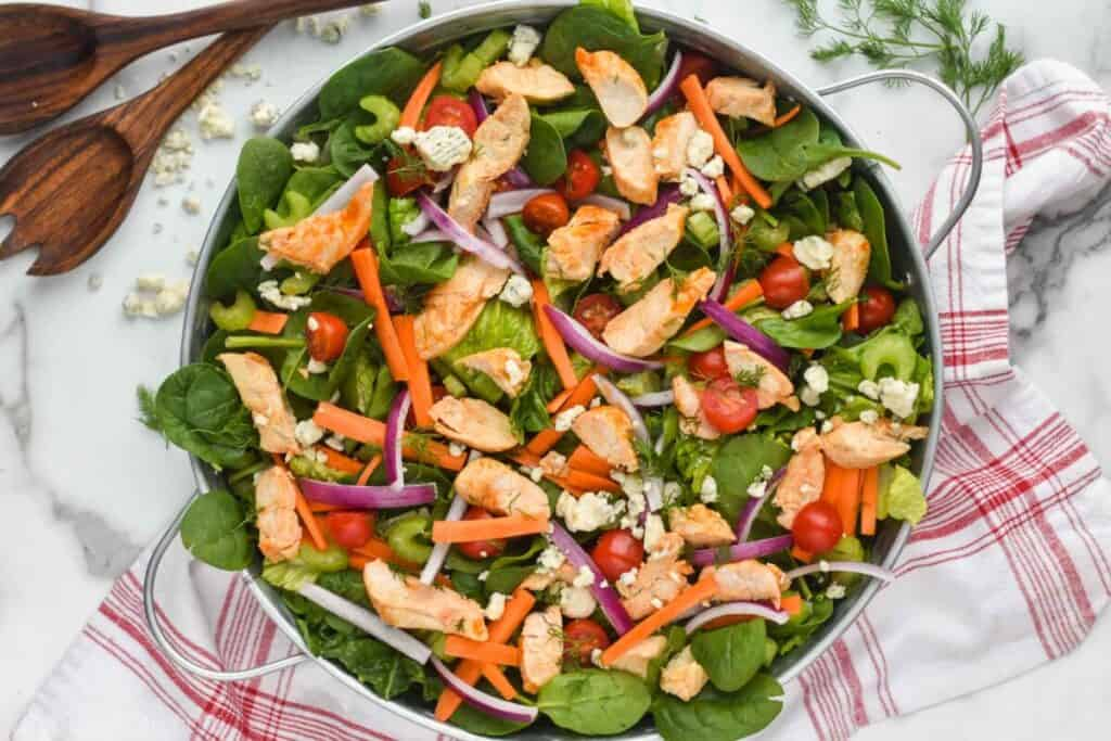 overhead of a buffalo chicken salad recipe in a galvanized metal try with buffalo chicken, spinach, romaine lettuce, carrots, red onions, and tomatoes