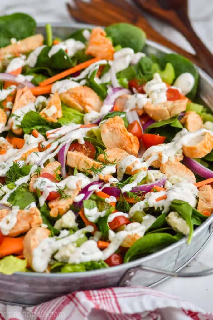 side view of a buffalo chicken salad in a galvanized metal try, dressed with homemade ranch dressing and full of fresh vegetables
