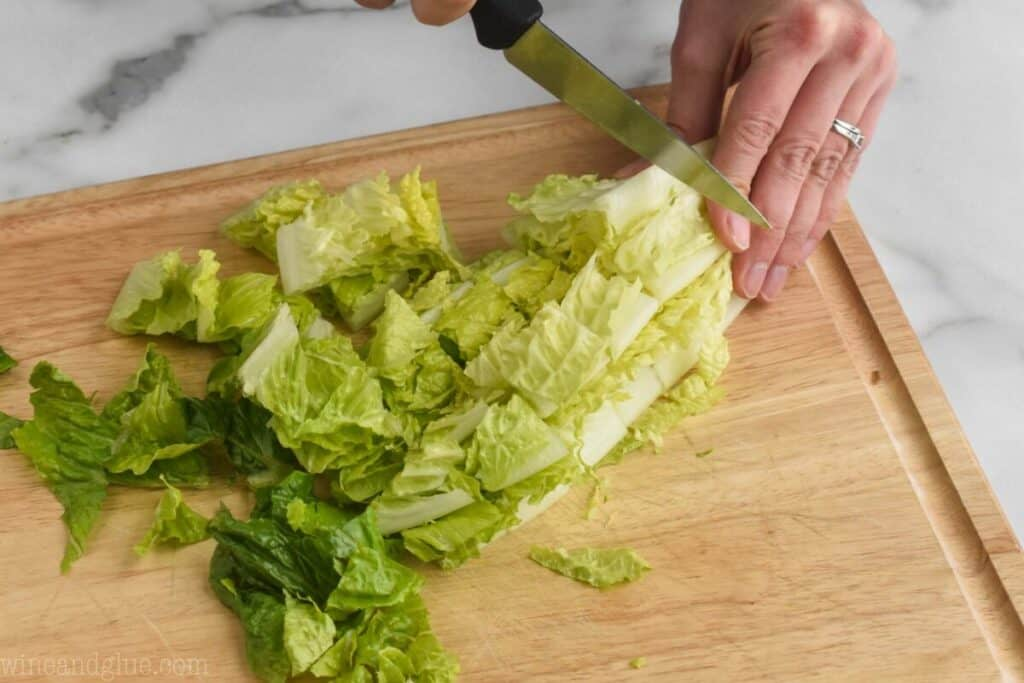 slicing a romaine heart width wise into strips for a salad