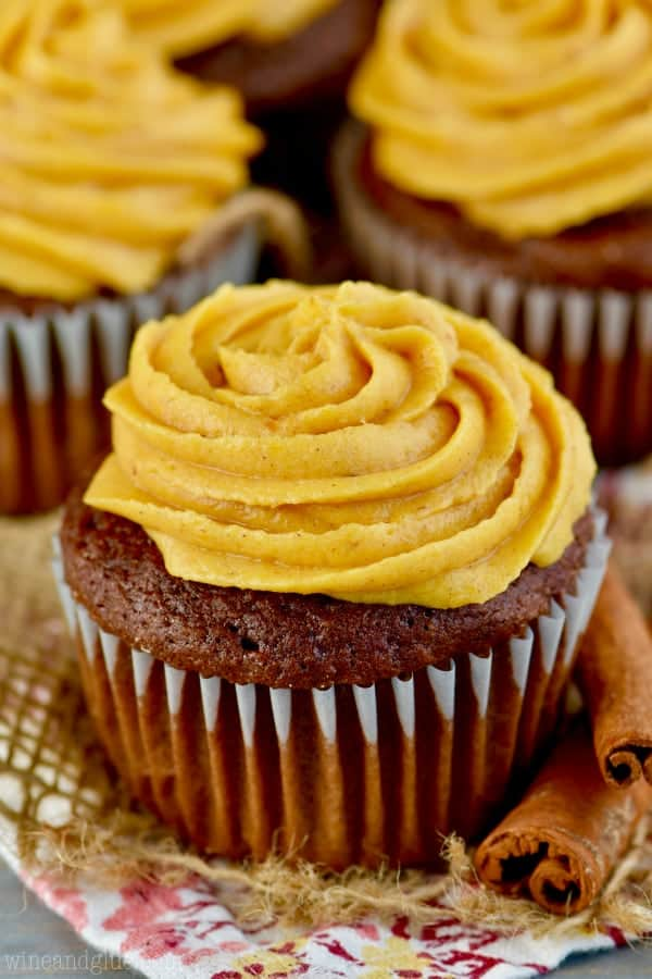 a chocolate cupcake with pumpkin frosting swirled in a rosette pattern