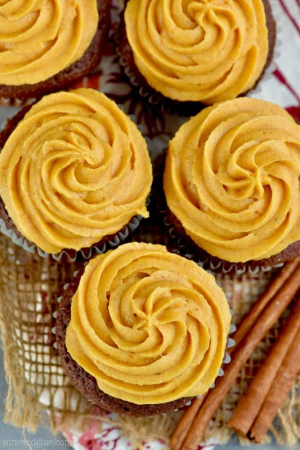 overhead look at five cupcakes that have pumpkin frosting piped in a rosette style on them