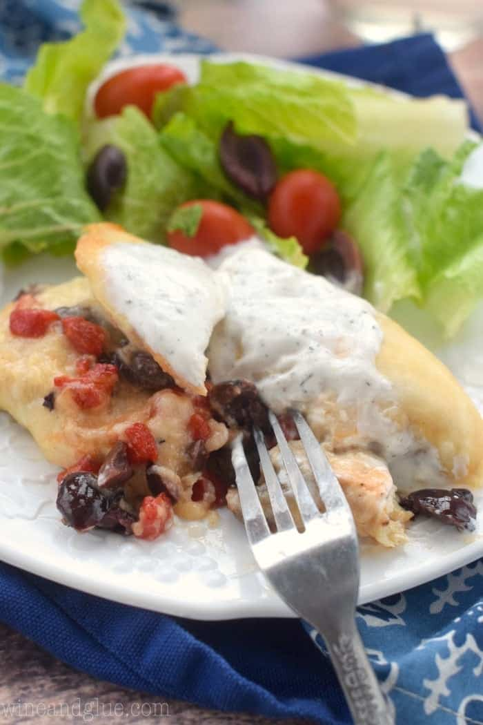 A fork cut into the Greek Stuffed chicken on one side of the plate. On the other is a salad with olives, cherry tomatoes, and lettuce.