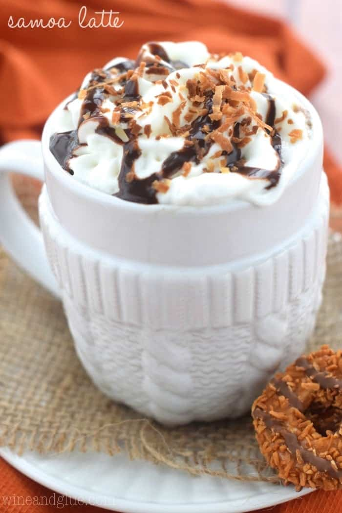 The Samoa Latte in a mug topped with whipped cream, chocolate drizzle, and toasted coconut toppings. On the side is one Samoa Cookies.