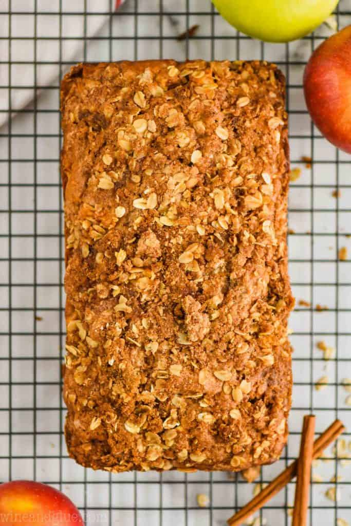 overhead view of apple bread that is covered in a streusel topping on a wire wrack with cinnamon sticks next to it