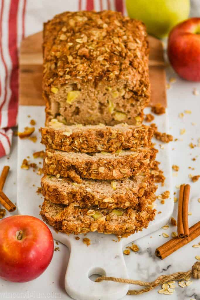 pulled back view of apple bread recipe that has been sliced into on a marble and wood cutting board with oats around, cinnamon sticks, and apples