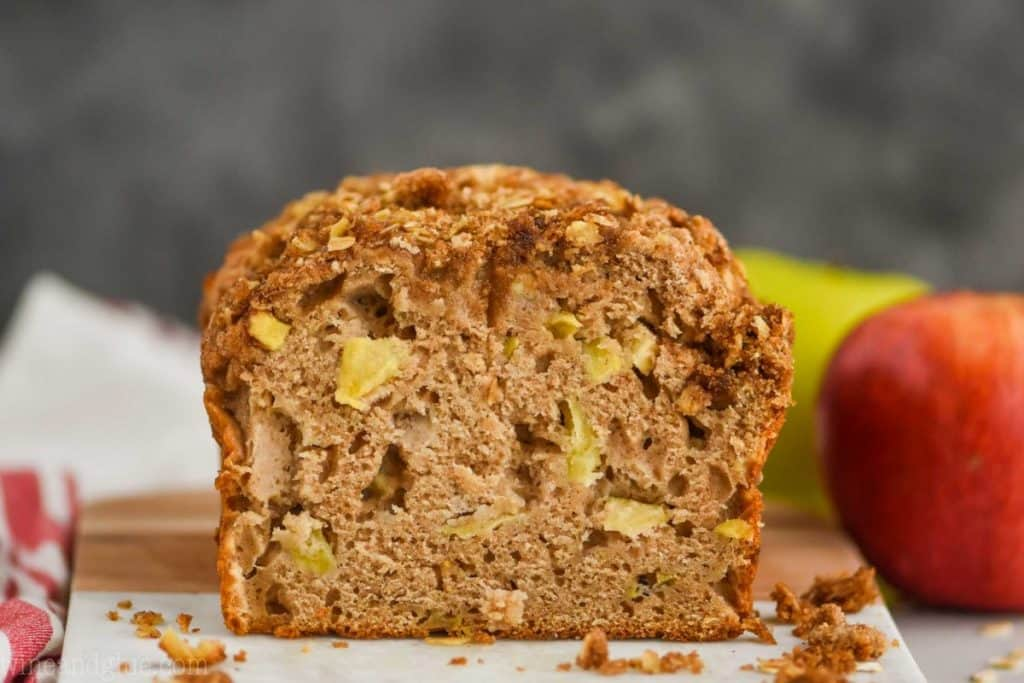 landscape photo of a cross section of apple cinnamon bread with apples in the background