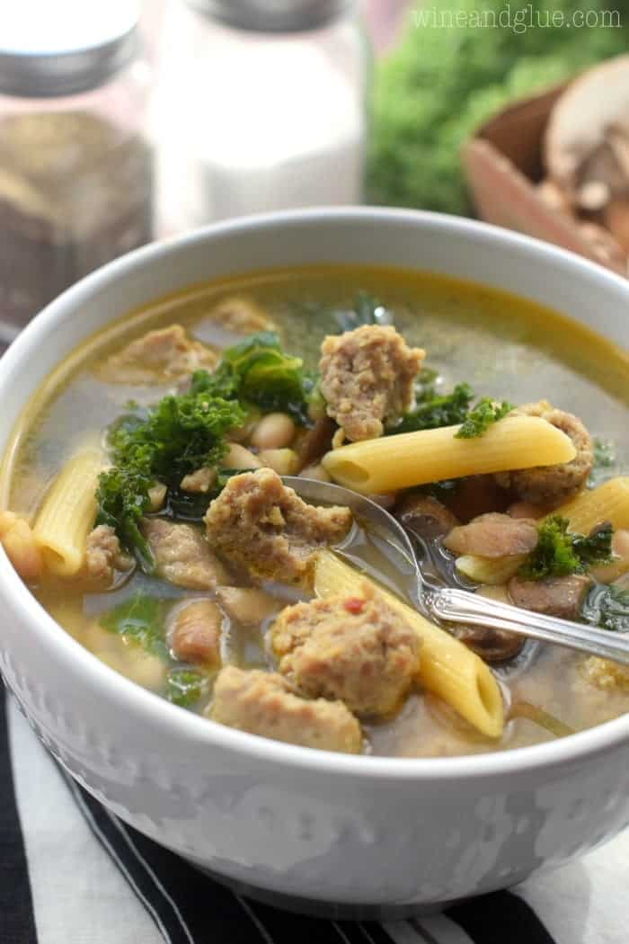 bowl of sausage and kale soup in a white bowl and spoon