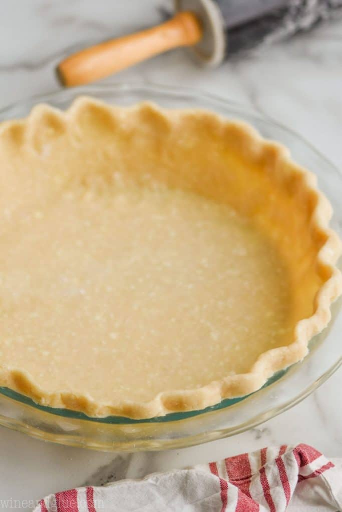 a pie crust recipe that has been rolled out, edges pinched, and placed in a clear pie pan
