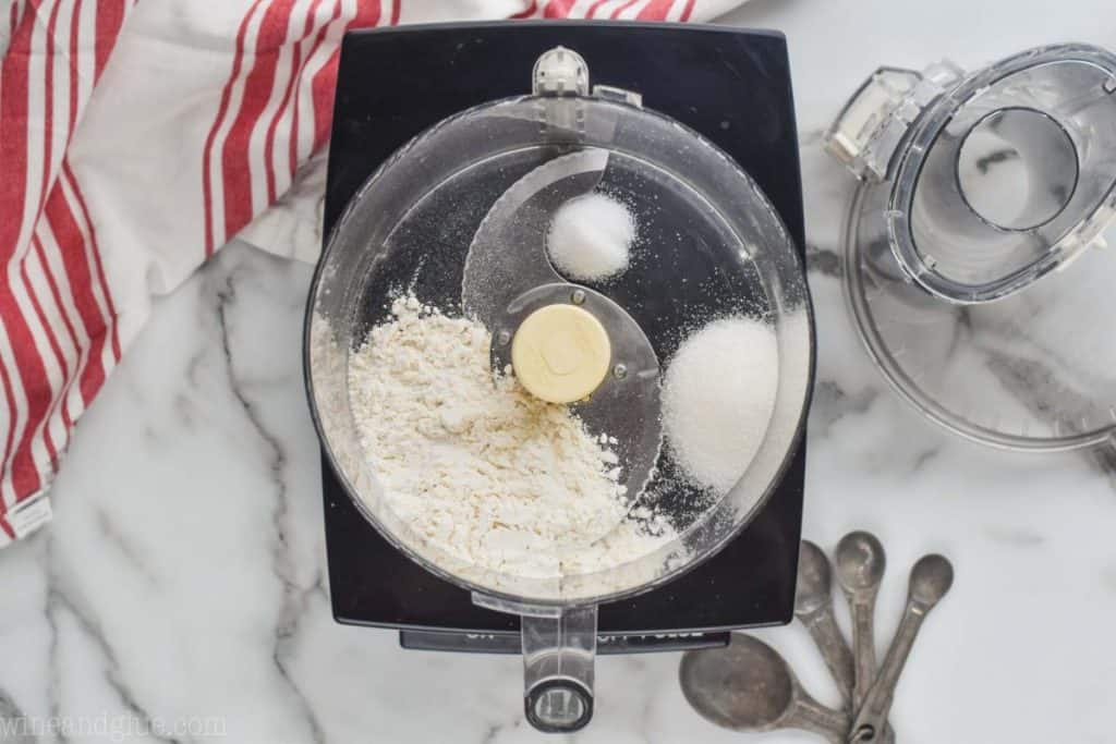 overhead view of a food processor with flour, sugar, and salt to create an easy pie crust
