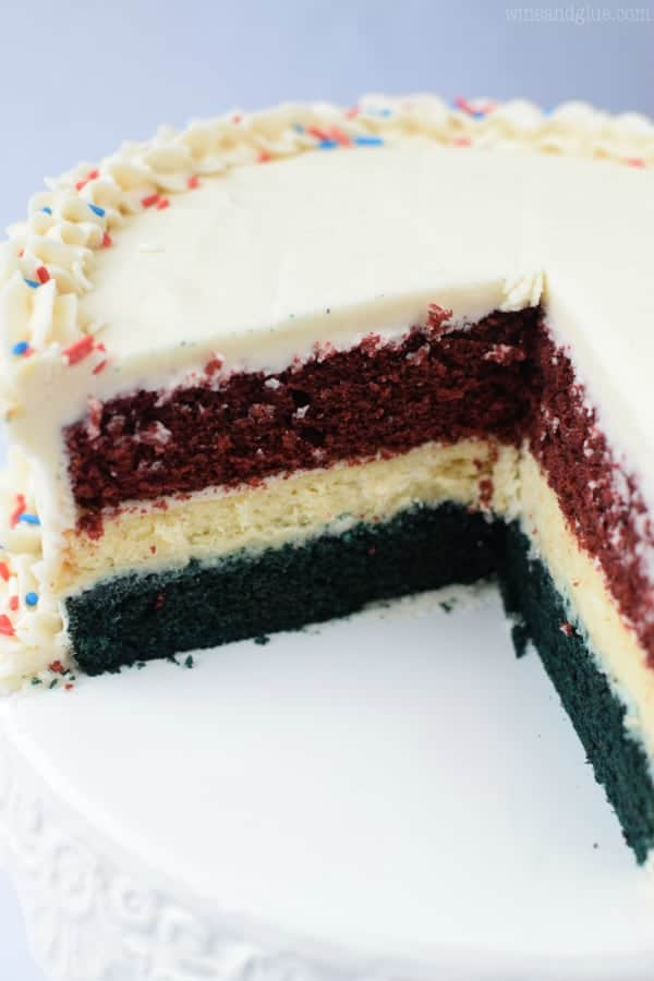 This Red, White, & Blue Velvet Cheesecake Cake is not just a huge show stopper, it is amazingly delicious! Two red velvet layers sandwich an amazing cheesecake layer, all covered in the most delicious vanilla buttercream frosting!