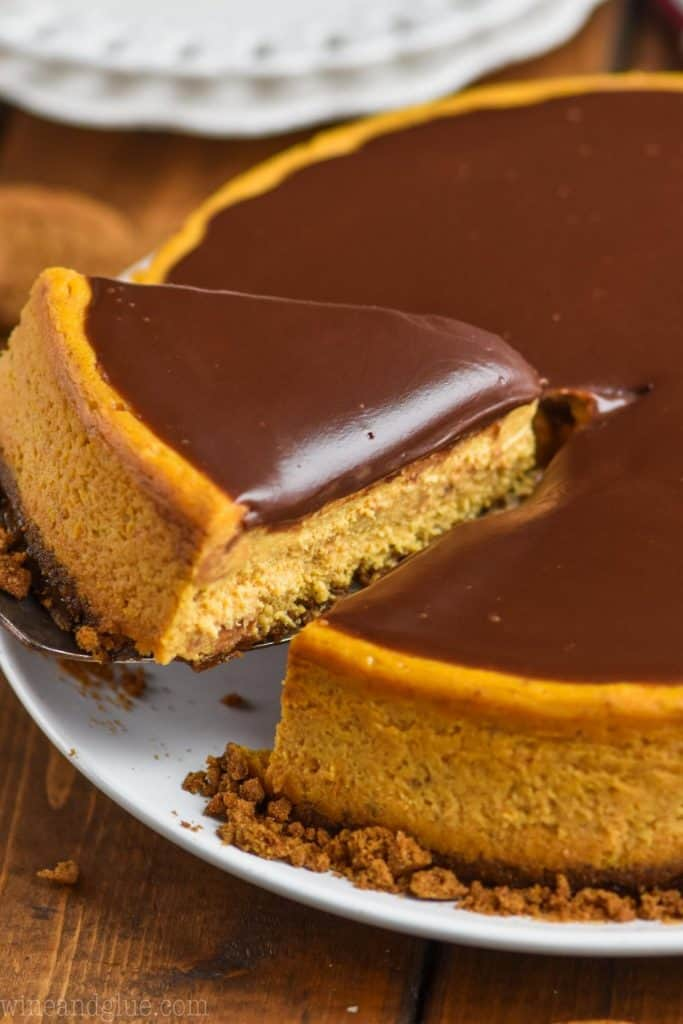 close up picture of side of the best pumpkin cheesecake with a piece being lifted out of it