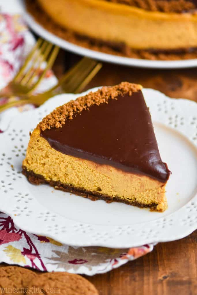 A piece of pumpkin cheesecake on a white plate topped with chocolate ganache