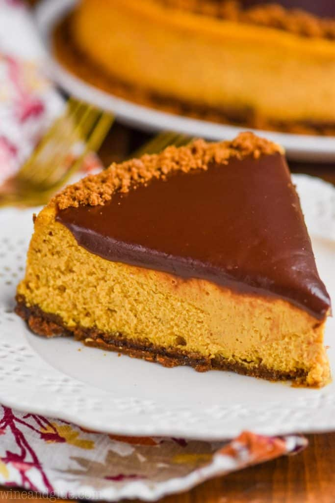 a piece of pumpkin cheesecake with chocolate ganache on top on a white plate