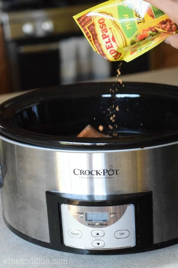 a packet of taco seasoning being poured into a slow cooker
