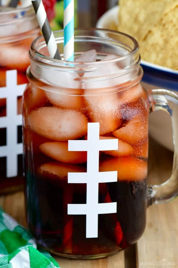 In a mason jar glass looking like a football, the Super Bowl Slammer has cubed ice in it with two paper straws.