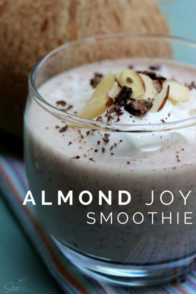In a large glass, the Almond Joy Smoothie is topped with cream, sliced almonds, and crushed chocolate bits.