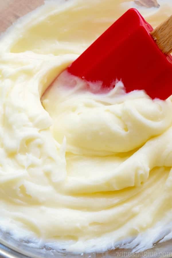 red spatula dipping into a bowl of cream cheese frosting
