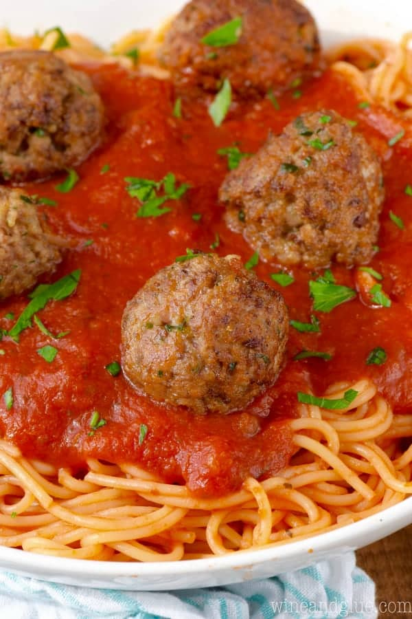 a close up of 6 meatballs on red sauce on spaghetti with fresh parsley as a garnish