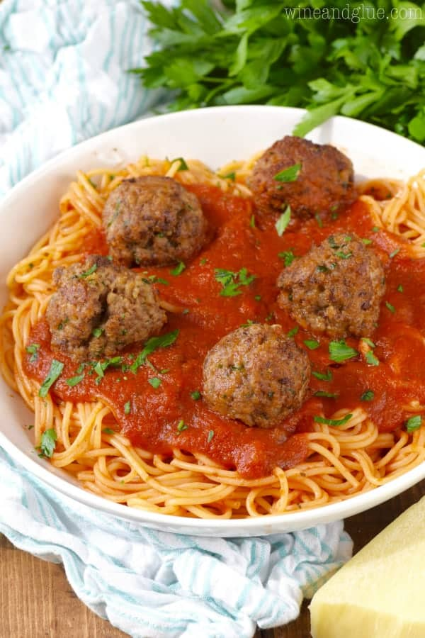 a white bowl filled with spaghetti and topped with red sauce and five Italian meatballs