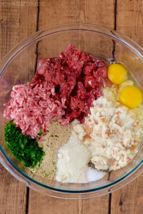 overhead view of a clear glass bowl filled with meat, eggs, soaked bread, fresh parsley, and breadcrumbs to make Italian meatballs