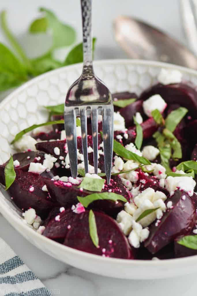 fork picking up a roasted beet in an bowl full of easy beet salad with feta cheese and fresh basil