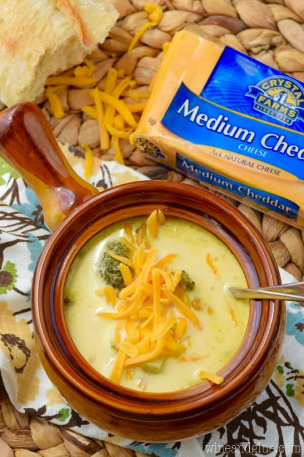 an overhead view of a brown soup bowl filled with crock pot broccoli cheddar soup with a block of cheddar cheese next to it