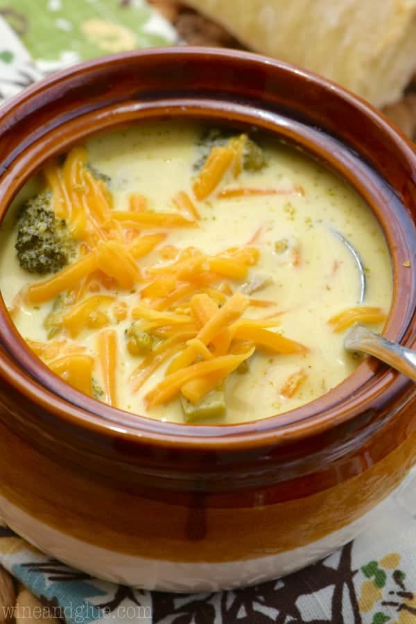 a close up of a brown bowl of broccoli cheddar soup topped with cheddar cheese