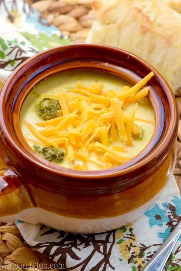 a small soup bowl filled with broccoli cheddar soup topped with shredded cheddar cheese.