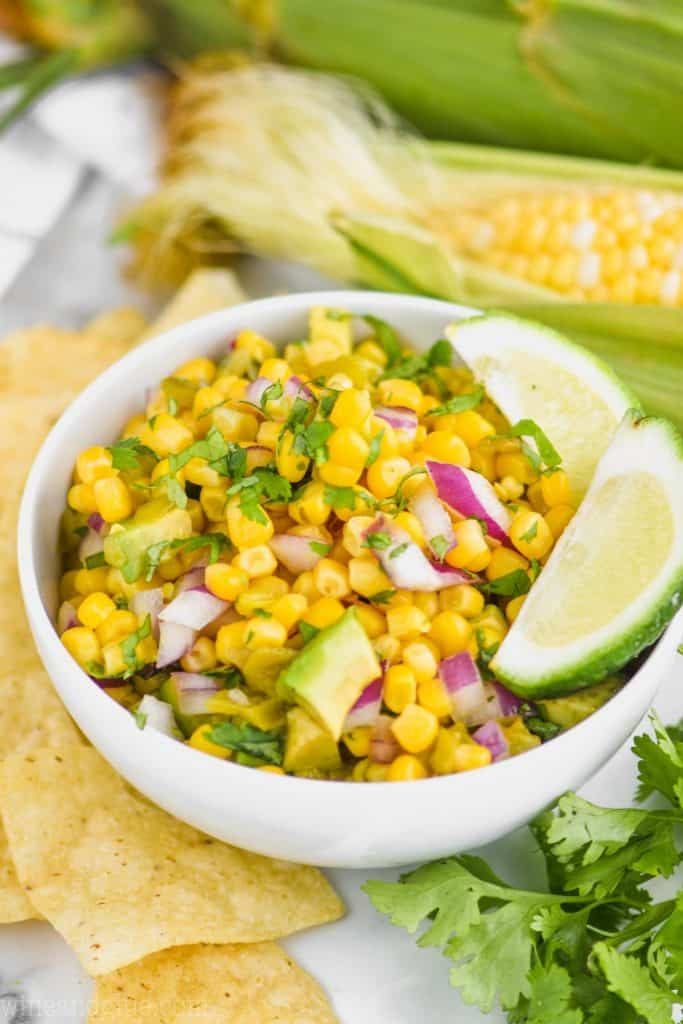 small white bowl with the best corn salsa recipe garnished with two lime wedges, corn on the cob in the background