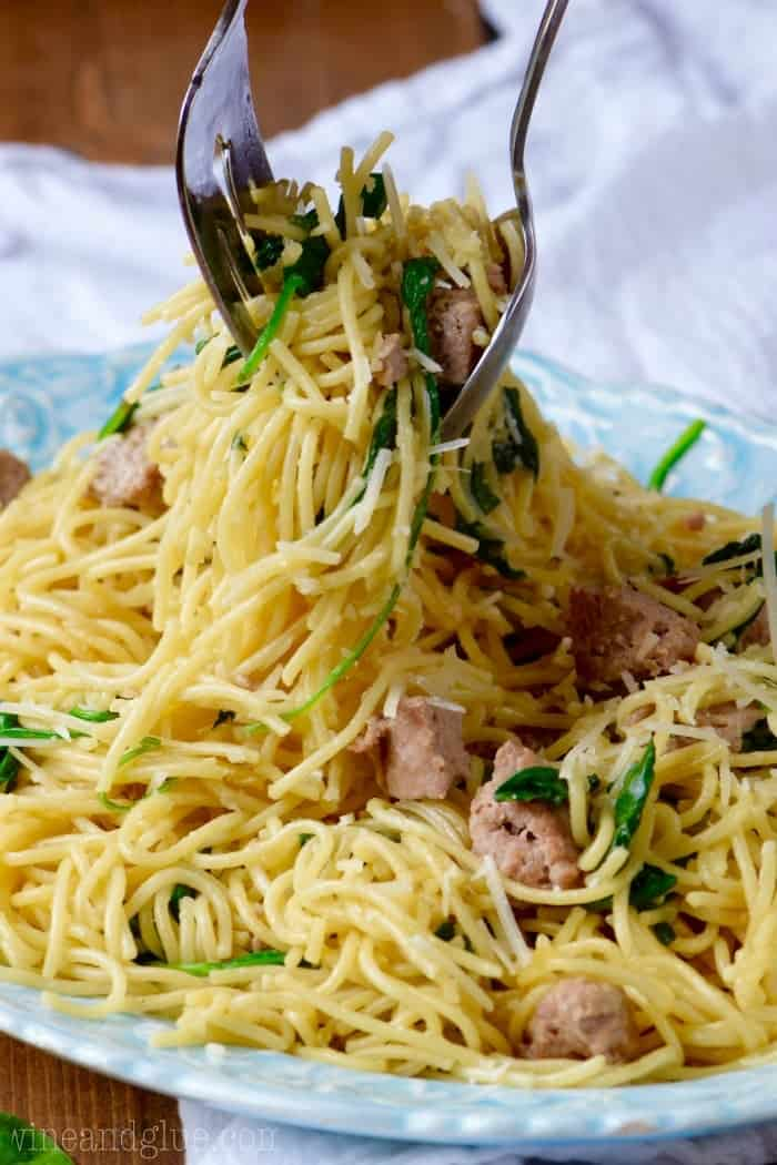 On a blue plate, a fork and a spoon is twirling to grab some of the One Pot Creamy Spaghetti and Sausage.