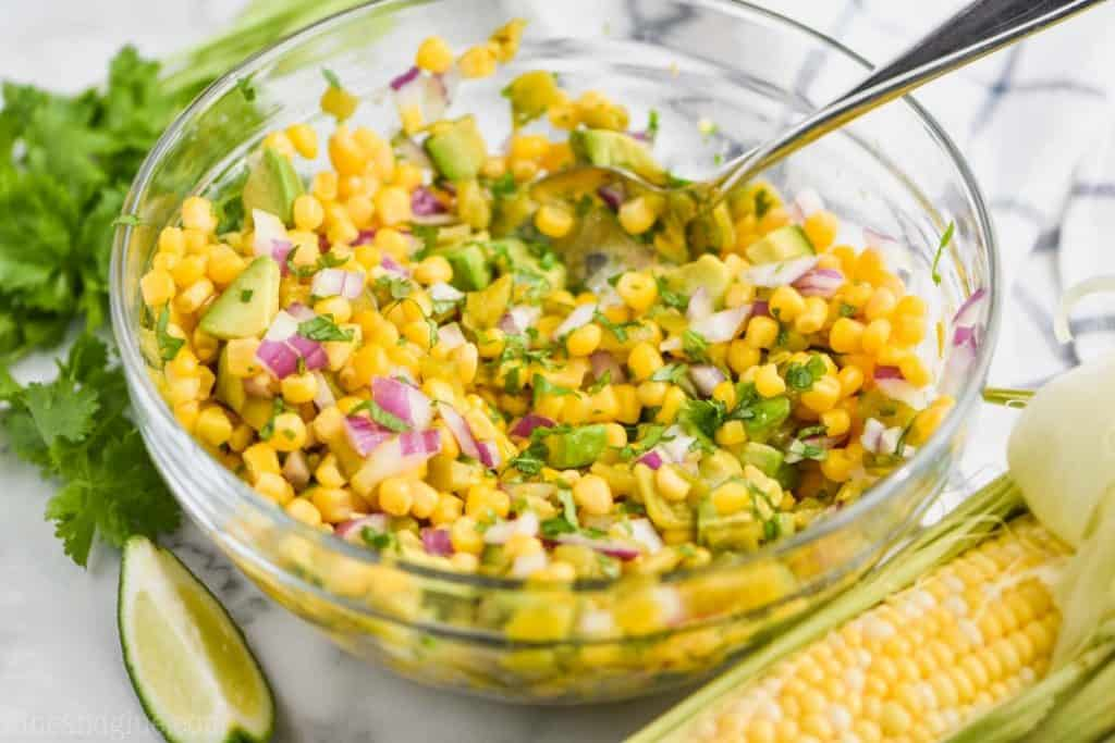 clear bowl full of avocado corn salsa