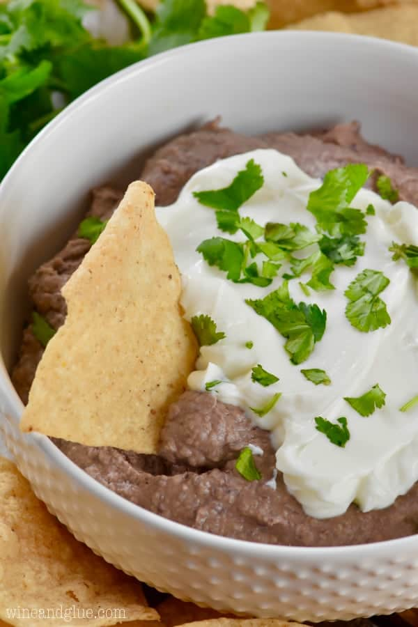 black bean dip in a white bowl with sour cream and cilantro