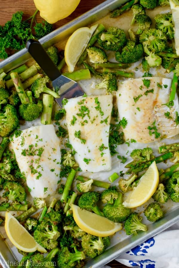 On a sheet pan, three baked cods have a golden crust surrounded by asparagus and broccoli.