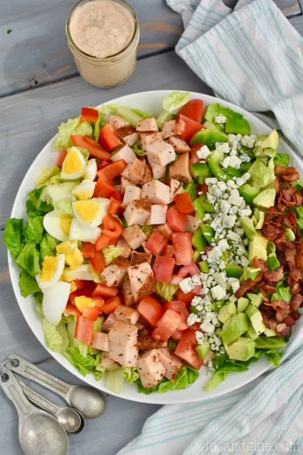 An overhead photo of the Cajun Cobb Salad topped with rows of hard boiled eggs, red peppers, cajun cobb, tomato, blue cheese, and bacon.
