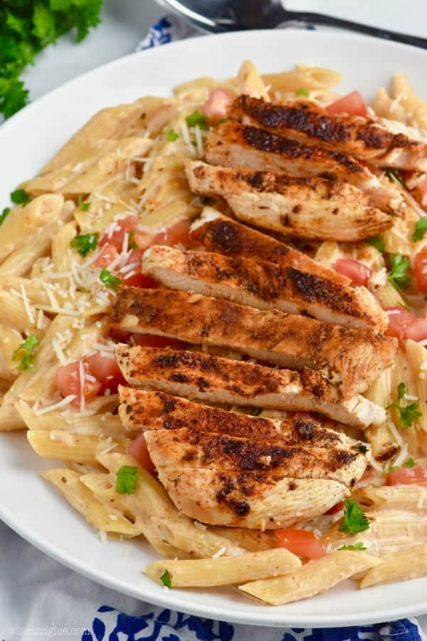 a close up of a plate of creamy cajun chicken pasta with the chicken blackened and cut up on a bed of pasta