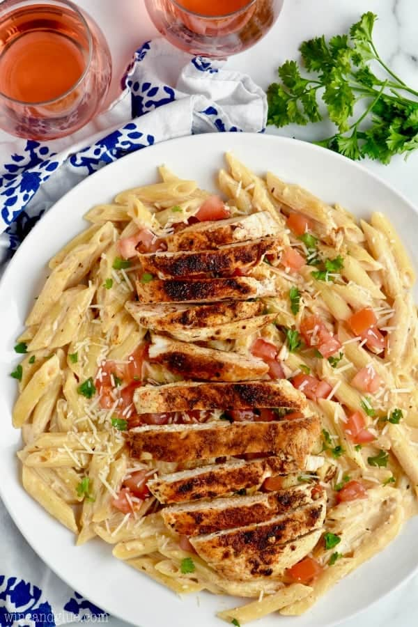 overhead view of a plate of spicy and creamy chicken pasta on a plate with two glasses of rose